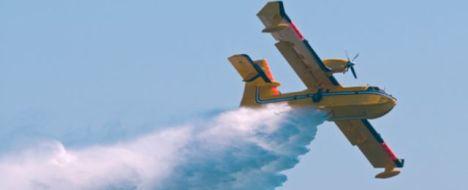 Samolot strażacki spuszcza wodę na płonący las